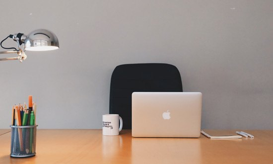 Photo d'un bureau de travail avec ordinateur et pot à crayons